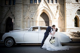 bride and groom kiss dip in front of white classic wedding car in front of chicago church