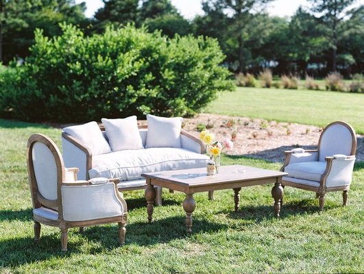 Wedding reception upholstered rental furniture on lawn with wood coffee table yellow flowers lounge
