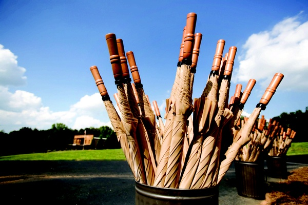 Tan umbrellas with wooden handles for an outdoor wedding ceremony