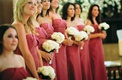 Bridesmaids at ceremony hold white rose bouquets