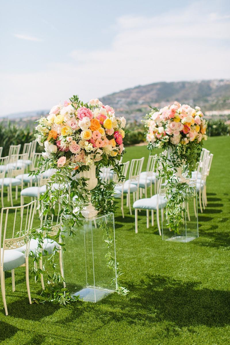 wedding ceremony laguna niguel acrylic riser pink orange yellow flower arrangements light blue chair