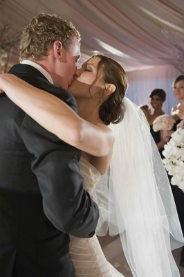 Bride in a veil kisses groom in a black tuxedo