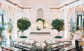 wedding reception vibiana long round tables trees altar decorated with greenery pillars centerpieces