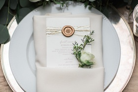 Wedding reception menu with gold wax seal, metallic strands with white rosebud in white napkin
