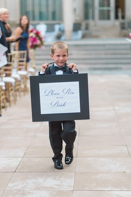 ring bearer in tuxedo carrying sign telling people to rise for the bride