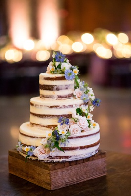 wedding cake naked design with cascading fresh flowers white pink purple blue on wood stand