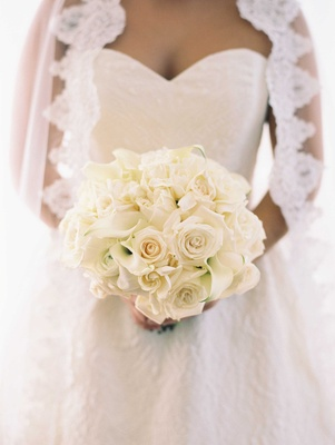 Bride with lace trim veil and sweetheart neckline holding white rose white calla lily bouquet