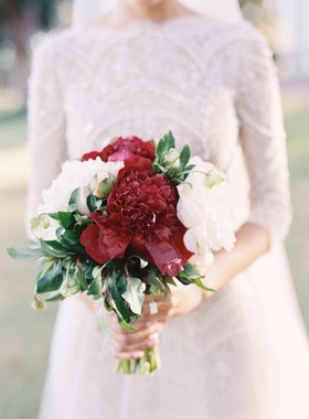 Bride carrying burgundy peony and white peony flower bouquet for wedding lace top and skirt dress