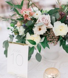 wedding reception white textured linen low centerpiece ivory pink flowers greenery gold white number