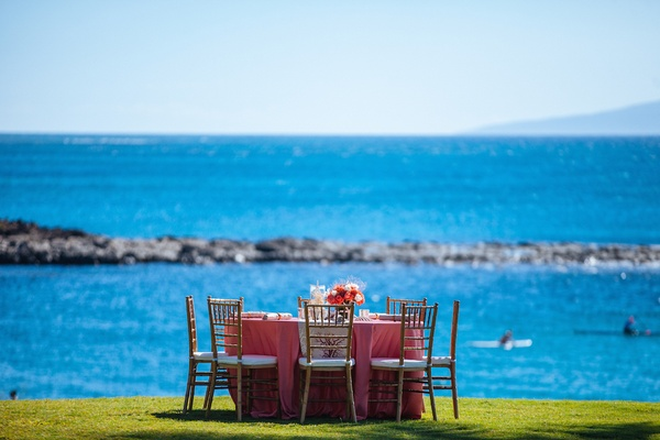 Guest table with pink tablecloth next to ocean