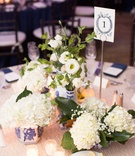 Wedding reception white texture linen tablecloth multiple arrangements of white flowers in jars