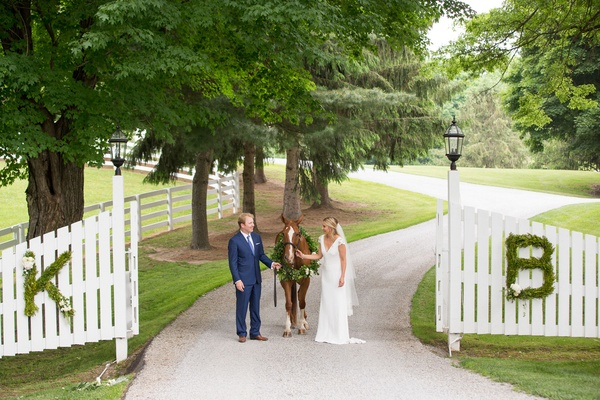 Bride in v neck cap sleeve wedding dress groom navy suit with horse wreath at farm monogram hedges
