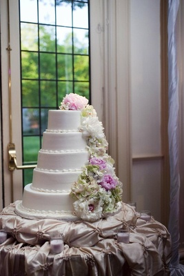 White wedding cake with white, pink, and green flowers and pears
