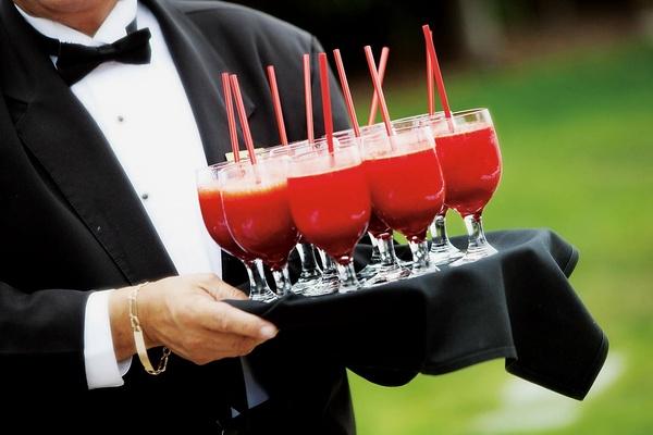 Tuxedo-clad caterer carrying platter of drinks