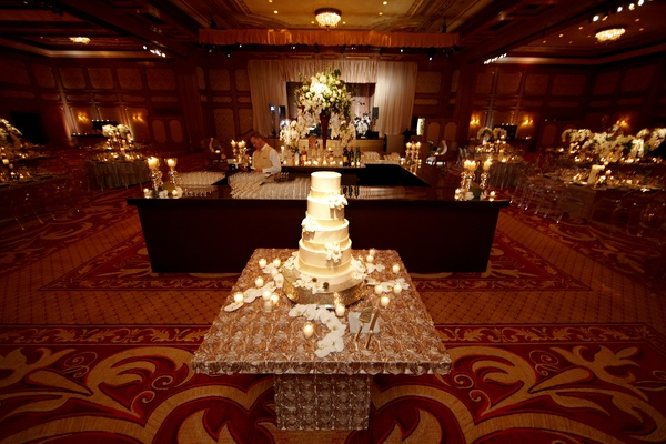 White cake on ballroom stand with flower petals