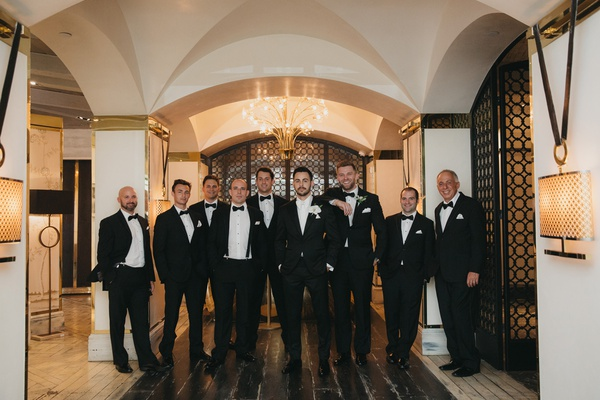 groom in white tie and tuxedo, groomsmen in black ties and tuxedos