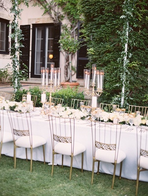 long tables white linens gold chairs white cushions low floral runner foliage gold candelabra covers