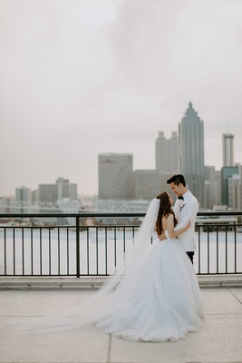 bride in tara keely ball gown wedding dress veil groom in white tuxedo jacket bow tie atlanta ga