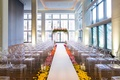 Wedding with ghost chairs ceremony lucite acrylic chairs and ceremony arch flowers bright colors