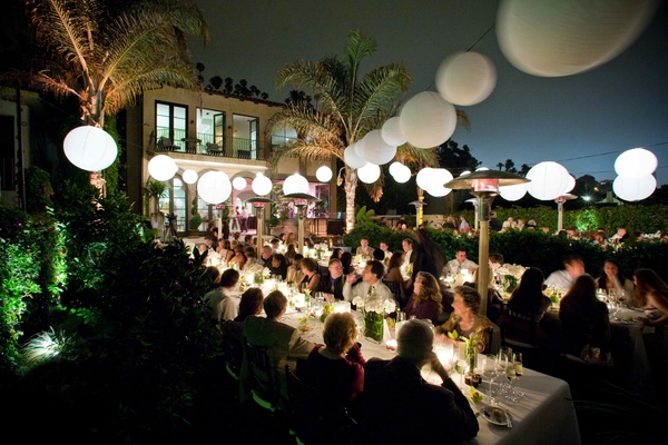Guests eat at outdoor reception table at night