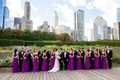 bride in lace v neck carolina herrera, groom in ralph lauren, bridesmaids in bright purple dresses
