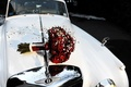 Bride's bouquet of red roses and crystals on the hood of a classic white Bentley