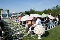 Ceremony guests hold multicolored parasols at wedding