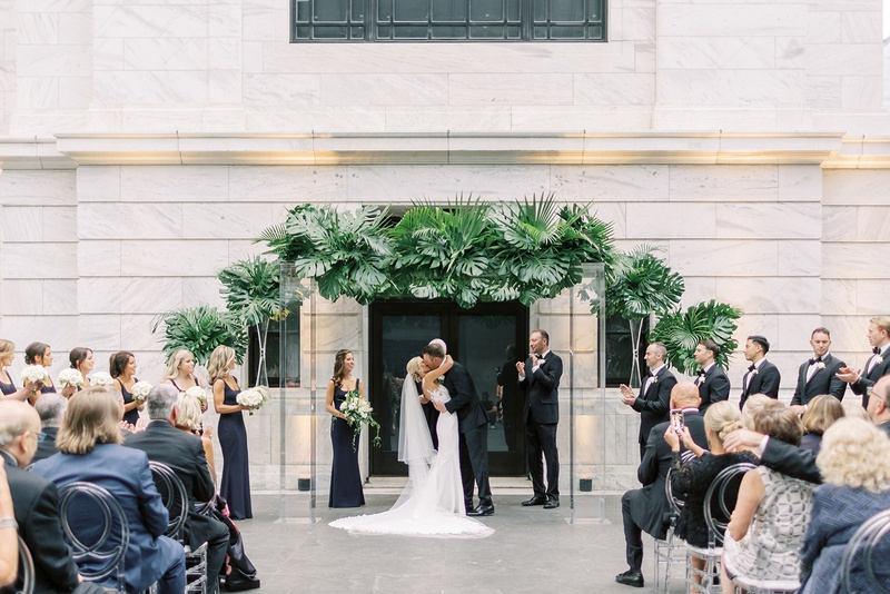 cleveland museum of art wedding ceremony tropical greenery arch modern decor guests oval lucite