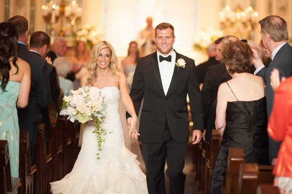 Bride in a strapless lace Isabelle Armstrong dress holds hands with Brian Leonard, running back