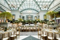 wedding reception at harold washington library in chicago greenery gold chairs skylight tall ceiling