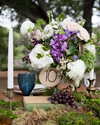 Table number etched on a piece of wood on white and purple flowers