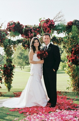 Bride and groom standing on rose petals