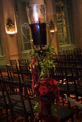Wrought iron stand decorated with greenery and red roses topped with red pillar candle