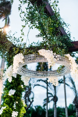 wedding ceremony arbor with round crystal chandelier decorated with white flowers greenery