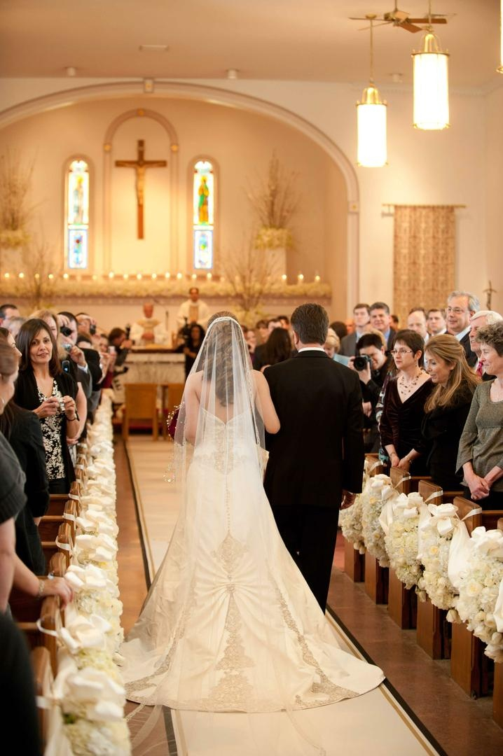 Bride in a veil and strapless dress with beading and lace details walking down the aisle with father
