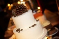 White wedding cake with snow sprinkles and pinecone cake topper