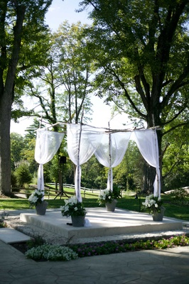 chuppa chuppah with white sheer fabric and potted white flowers at outdoor ceremony