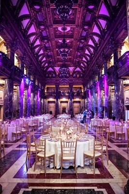 Tall elegant ceilings with violet lighting and gilt chairs