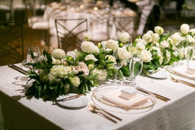 white rectangular table with garland runner of white flowers and greenery