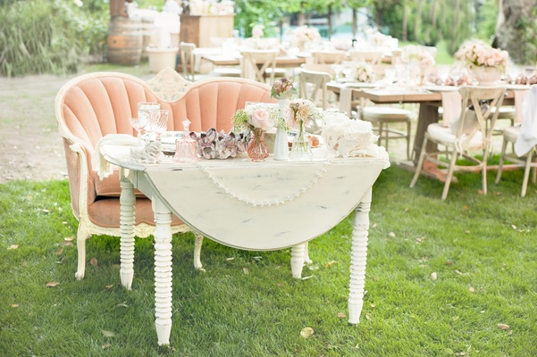 Antique white table with pink settee bench at outdoor wedding