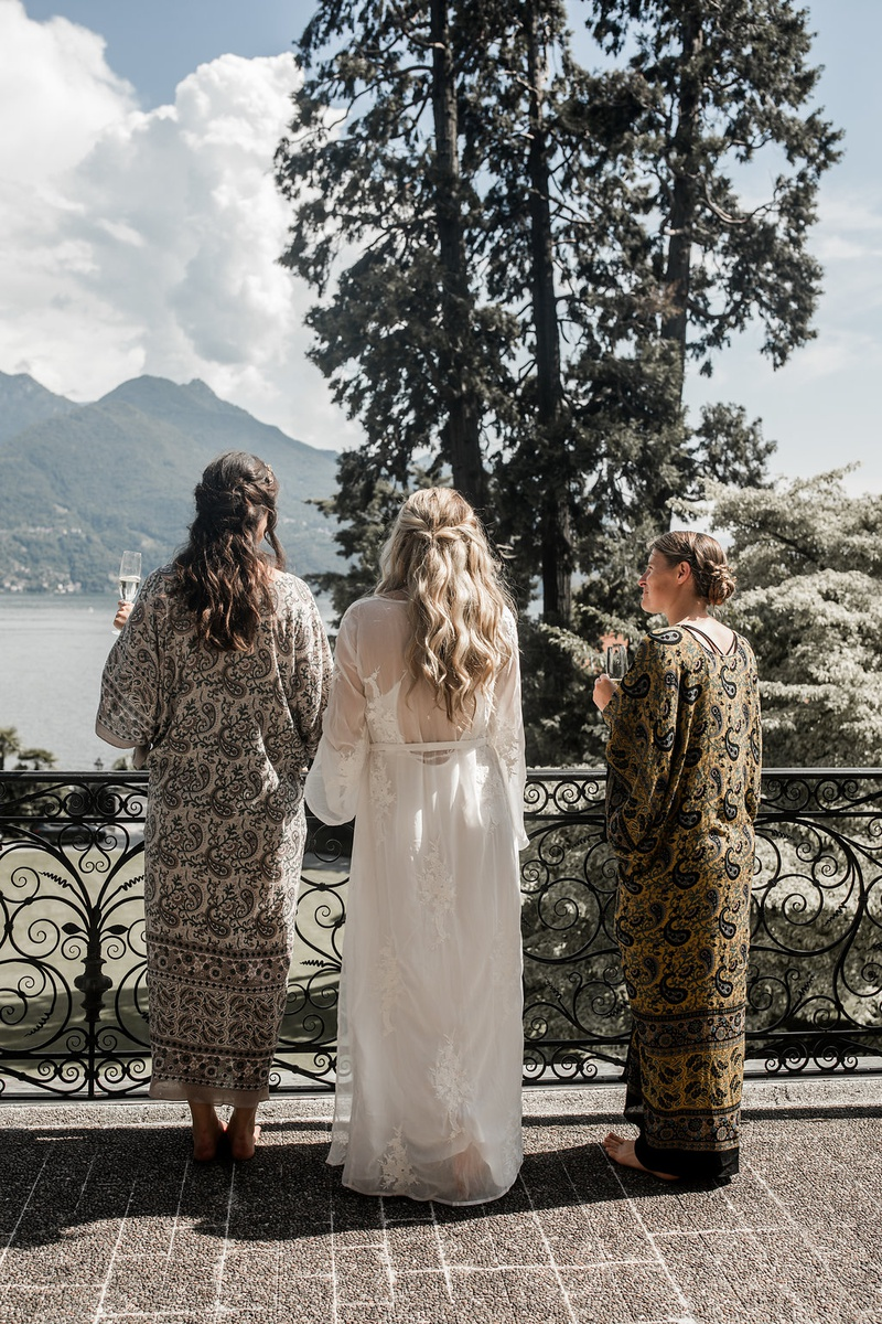 bride in long white robe and bridesmaids looking over lake como with champagne in hand
