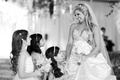 Black and white photo of bride smiling at flower girls