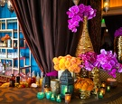 Gold textured vases with hot pink orchids, calla lilies, orange chrysanthemums, colorful lanterns