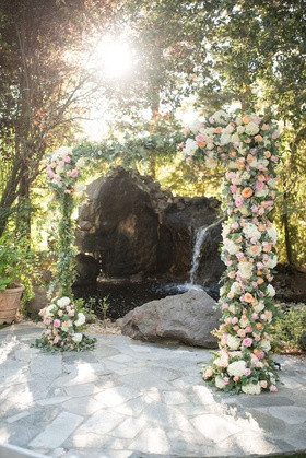 wedding ceremony arch with pond and waterfall backdrop greenery white hydrangea pink orange roses