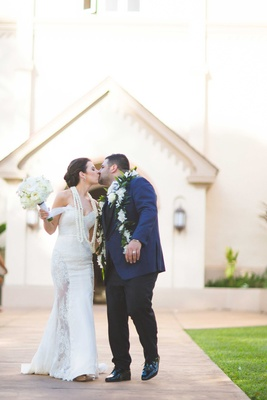 Bride and groom kiss wearing Hawaiian leis after leaving church Catholic wedding ceremony