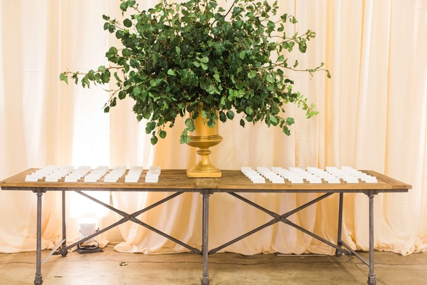 Bare wood table industrial with gold urn filled with green leaves white escort cards on top