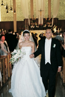 Newlyweds hold hands walking up aisle of church