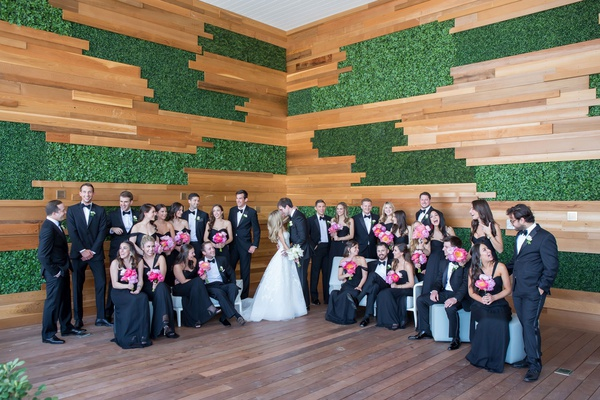Wedding party in black tie attire tuxedo bow tie wood greenery wall decor