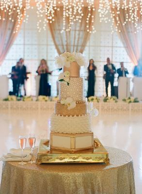 Wedding cake white and gold different tiers white flowers champagne gold cake table