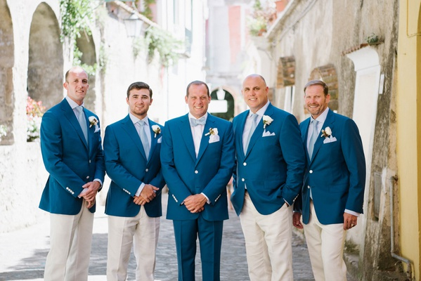 Groom in blue suit with bow tie groomsmen in blue jacket khaki pants and blue ties boutonniere italy